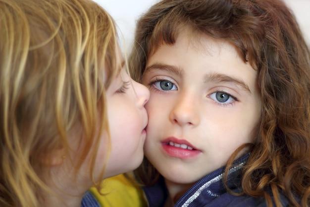 Blond meisje dat haar dochter blauwe ogen kust