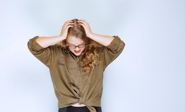 Blond meisje dat haar hoofd vasthoudt, ziet er doodsbang en uitgeput uit.