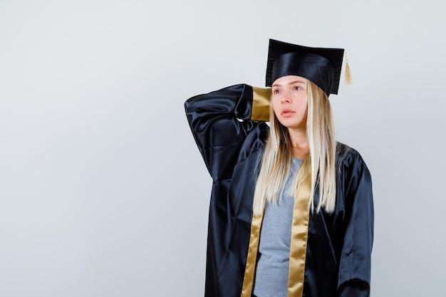 Blond meisje dat hand achter haar hoofd zet, aan iets denkt in afstudeerjurk en pet en peinzend kijkt