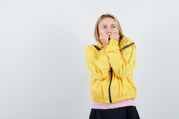 Blond meisje dat handen op de mond legt, aan iets denkt in roze t-shirt en gele jas en peinzend kijkt.