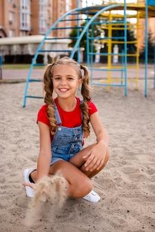 Blond meisje dat met zand tot de camera werpt