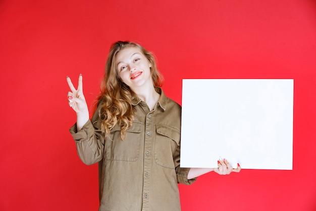 Blond meisje dat naar een canvas kijkt en ervan geniet.