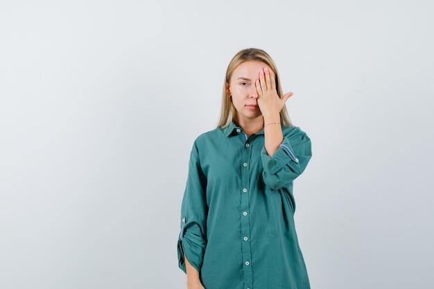 Blond meisje dat oog bedekt met hand in groene blouse en er serieus uitziet