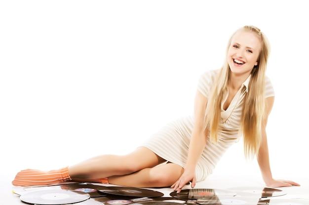 Blond meisje dat op wit met vinylverslagen legt