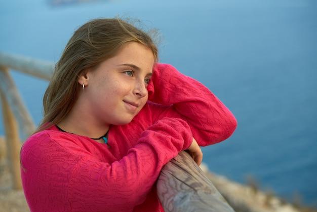 Blond meisje dat overzees van een vooruitzichtpunt kijkt