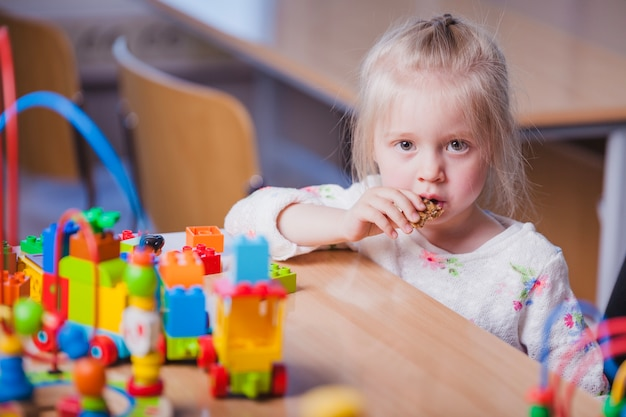 Blond meisje dat speelgoed in de mond legt