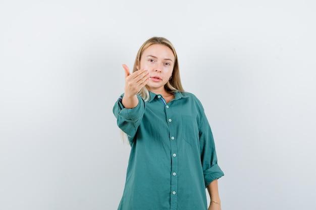 Blond meisje dat uitnodigt om in een groene blouse te komen en er vriendelijk uitziet