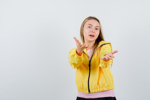 Blond meisje dat uitnodigt om in roze t-shirt en geel jasje te komen en er vriendelijk uitziet.
