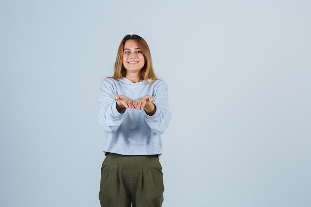 Blond meisje dat uitnodigt om te komen in olijfgroen blauw sweatshirt en broek en er vriendelijk uitziet. vooraanzicht.