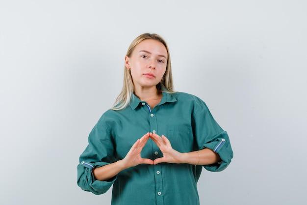 Blond meisje dat verzekeringsgebaar in groene blouse toont en er stralend uitziet