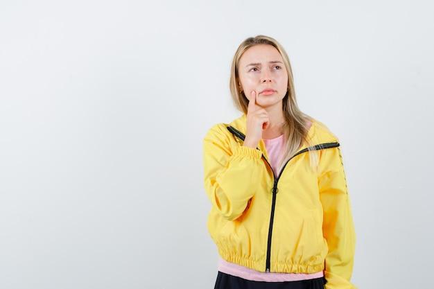 Blond meisje dat wijsvinger in de buurt van mond zet, aan iets denkt in roze t-shirt en gele jas en peinzend kijkt.