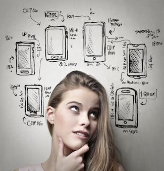 Blond meisje dat zich over smartphones afvraagt
