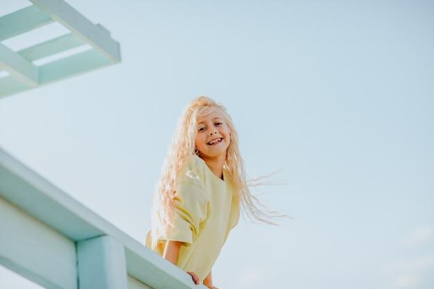 Blond meisje die zich voordeed op de badmeestertoren met blauwe hemelachtergrond