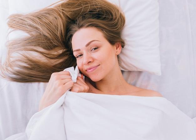 Blond meisje die zich voordeed op het bed