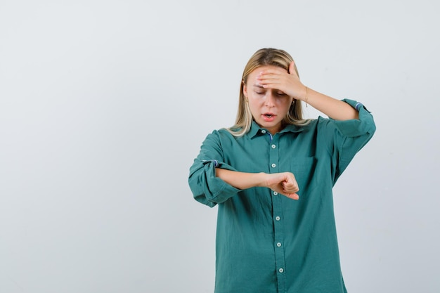 Blond meisje doet alsof ze naar de klok kijkt terwijl ze de hand op het voorhoofd legt in een groene blouse en er verbaasd uitziet