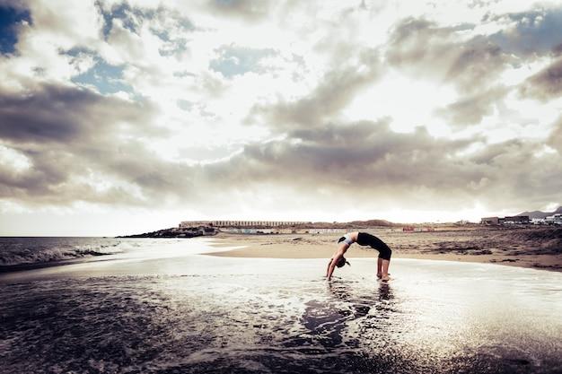 Blond meisje doet brugpositie op het strand