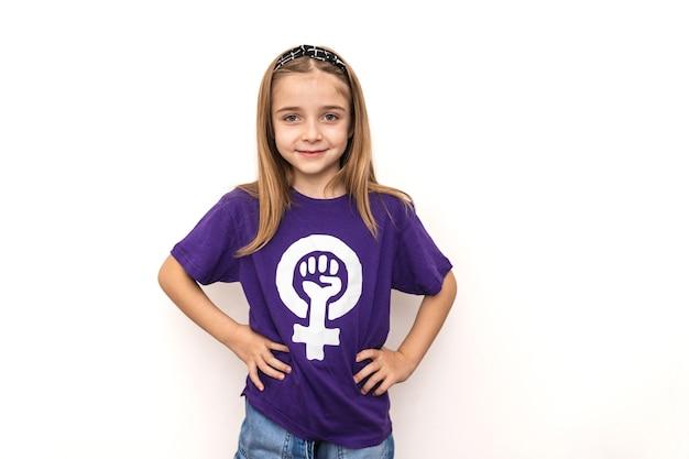 Blond meisje draagt een paars t-shirt met het symbool van de internationale feministische vrouwendag op een witte muur