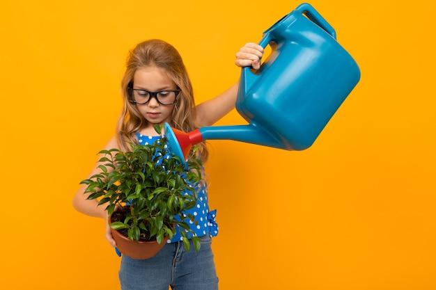Blond meisje drenken een blad plant uit een gieter op een gele achtergrond.