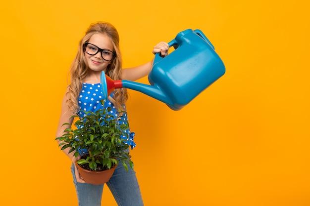 Blond meisje drenken een blad plant uit een gieter op een oranje muur