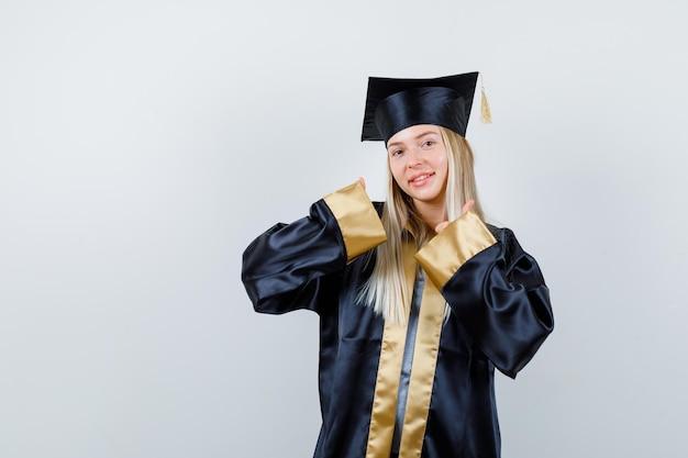Blond meisje duimen opdagen met beide handen in afstudeerjurk en pet en er schattig uitzien.