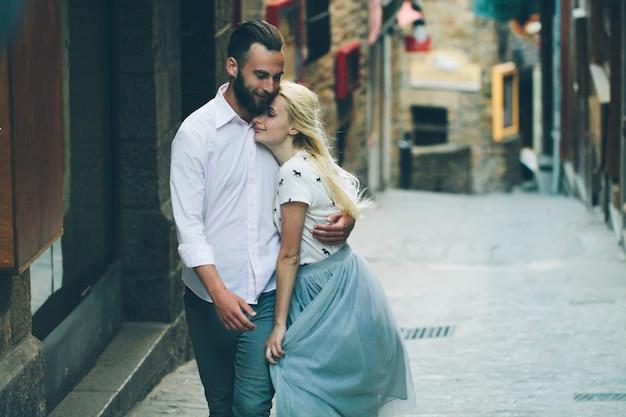 Blond meisje en hipster knappe man met baard knuffelen en zoenen op de straten van de stad