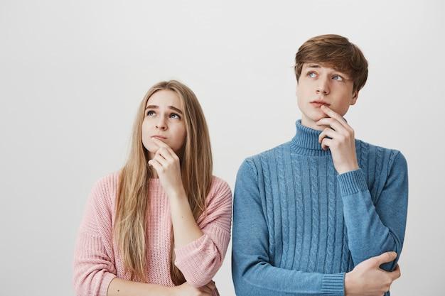 Blond meisje en jongen kijken linksboven, denken, besluit nemen
