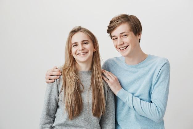 Blond meisje en jongen met beugels lachen, glimlachen en knuffelen