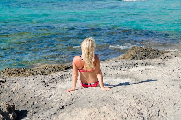 Blond meisje geniet op het strand. achterkant van de jonge vrouw tegen blauwe zee.
