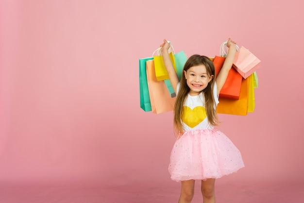 Blond meisje geniet van haar winkelen op een pastel roze achtergrond met copyspace. uitverkoop. schattig klein meisje met veel veelkleurige boodschappentassen in de studio.