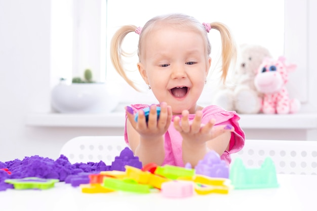 Blond meisje glimlacht en speelt met paars zand op een witte tafel.