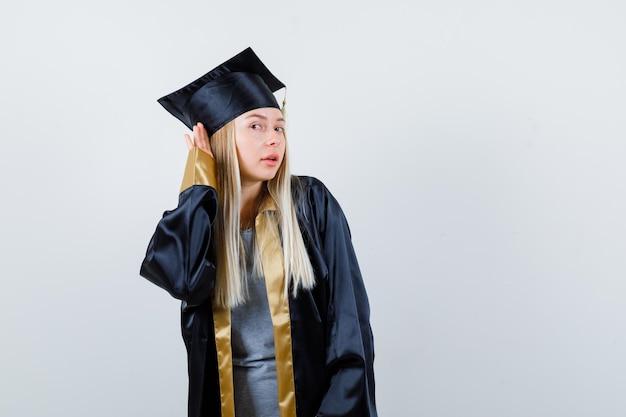 Blond meisje hand in hand in de buurt van oor om iets te horen in afstudeerjurk en pet en er gefocust uit te zien.