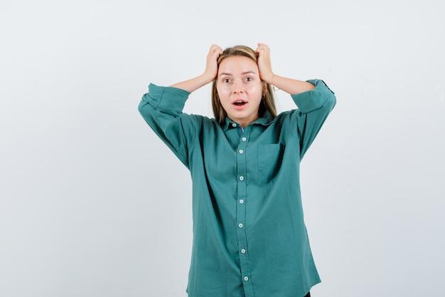 Blond meisje hand in hand op het hoofd in groene blouse en kijkt verrast.