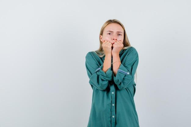 Blond meisje handen op mond zetten in groene blouse en geschokt kijken