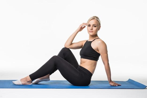 Blond meisje heeft een ontspannen tijd na sportoefening op de vloer zittend op een sportkaart