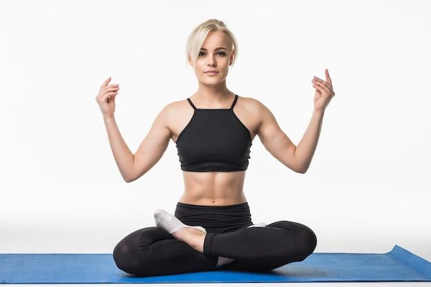 Blond meisje heeft een ontspannen yoga-tijd na sportoefening op de vloer zittend op een sportkaart