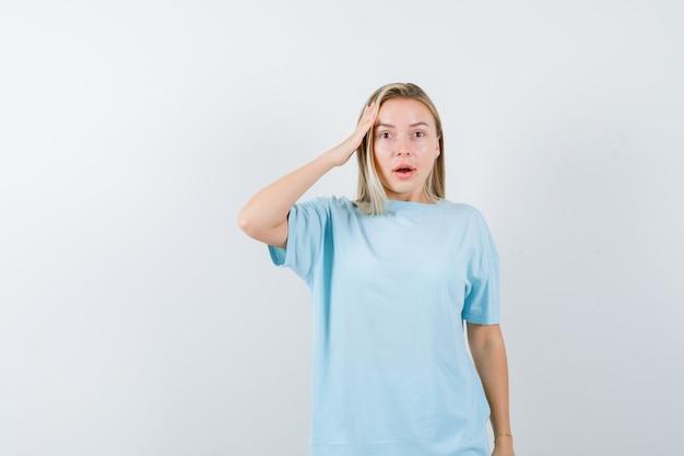 Blond meisje houdt de hand op tempel in blauw t-shirt en kijkt verbaasd. vooraanzicht.