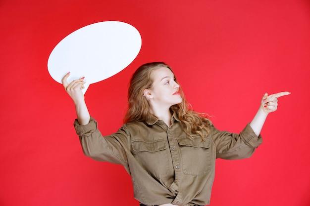 Blond meisje houdt een ovale denkbord vast en wijst erop.