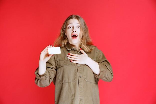 Blond meisje houdt een visitekaartje vast en stelt zichzelf voor.