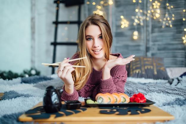 Blond meisje houdt eetstokjes vast en lacht naar voren