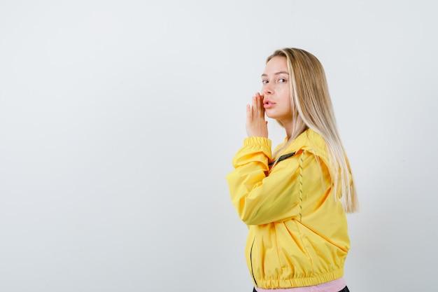 Blond meisje houdt hand dichtbij oor om iets in roze t-shirt en geel jasje te horen en gefocust op zoek