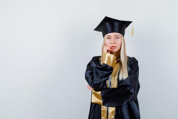Blond meisje in afgestudeerd uniform staat in denkende pose en ziet er verstandig uit