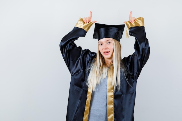 Blond meisje in afstudeerjurk en pet die met wijsvingers omhoog wijst en er schattig uitziet