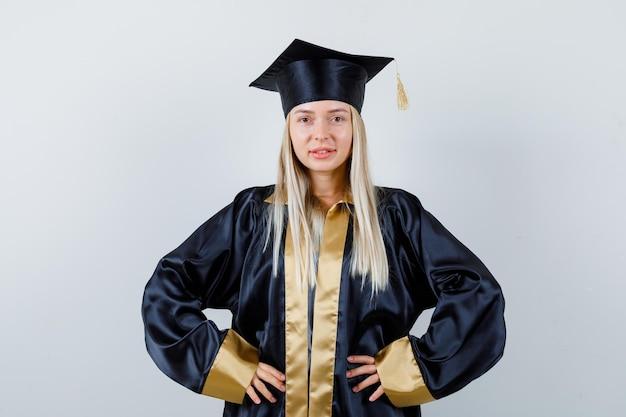 Blond meisje in afstudeerjurk en pet hand in hand op taille en ziet er zelfverzekerd uit