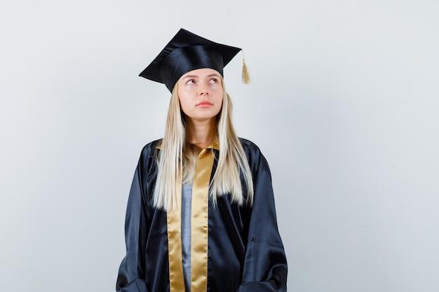 Blond meisje in afstudeerjurk en pet staat rechtop, kijkt weg en poseert voor de camera en kijkt peinzend