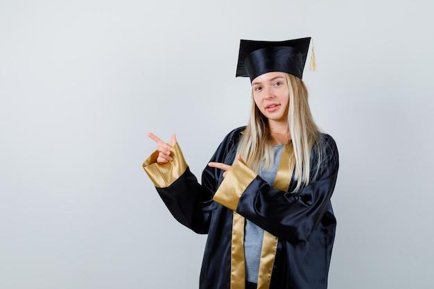 Blond meisje in afstudeerjurk en pet wijst naar links met wijsvingers en ziet er schattig uit