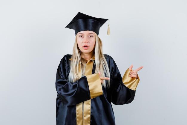 Blond meisje in afstudeerjurk en pet wijst naar rechts met wijsvingers en kijkt verrast looking