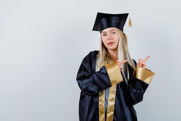 Blond meisje in afstudeerjurk en pet wijst naar rechts met wijsvingers en ziet er schattig uit