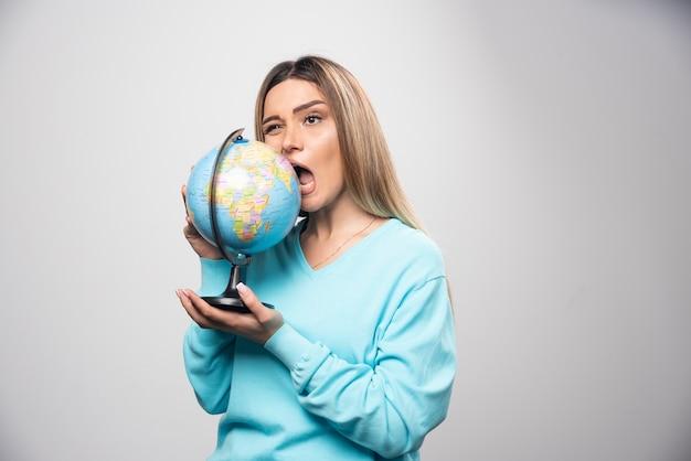 Blond meisje in blauw sweatshirt houdt een wereldbol vast en bijt erin