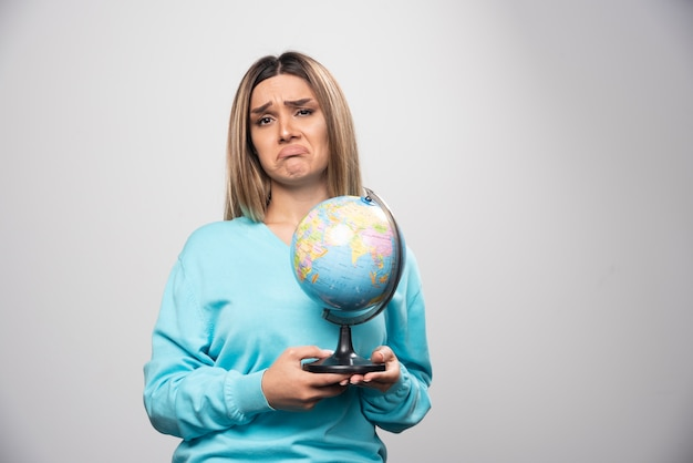 Blond meisje in blauw sweatshirt houdt een wereldbol vast en ziet er onzeker en verward uit.
