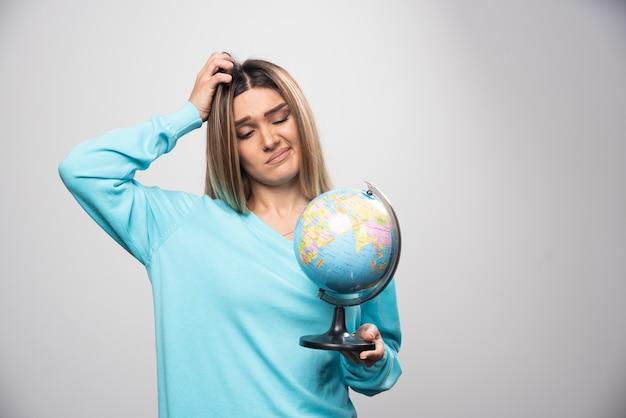 Blond meisje in blauw sweatshirt houdt een wereldbol vast en ziet er onzeker en verward uit